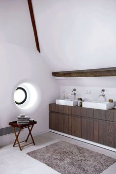 Gorgeous wood vanity and cute round window for this bathroom in a barn conversion. Petit hublot pour cette salle de bains blanc et bois
