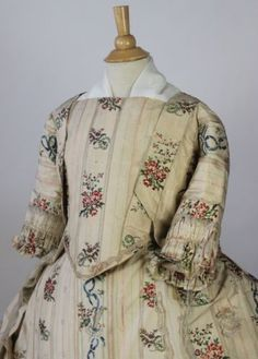 18th Century Sacque Back Gown, Brocade Harp and Floral Silk from 1750-1780 Museum deaccessioned from the Metropolitan Museum of Art. Three Piece Gown Including Stomacher, Petticoat and Robe with Harp and Floral Silk Brocade! Amazing hand stitched floral brocade with harps and floral design. Cream taffeta having polychrome brocade floral stripe with harps, cornucopias and lace trim. There are slits on each side of the skirt for the usage of pockets, these slits are reinforced with lining and…