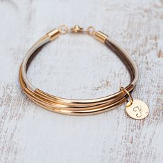 Elegant casual 3 bangle bracelet with 2 mm leather cord and gold tube 3x50mm and one gold disc with initial on golden disc 12mm The colors of the cords