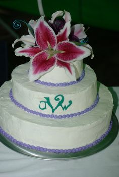 A lemon cake with raspberry filling topped with lilies and inscribed with our new initials on the front