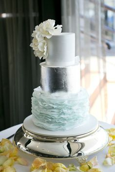 Three tiered wedding cake, White, Silver and Blue with gorgeous ruffle detailing. By, Cupcakes and Cakes