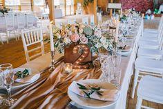 Оформление стола гостей в стиле рустик: композиция в коробке, бежевый раннер на стол, оформление салфетки веточкой оливы и деревянной табличкой с именем гостя, а также необычный номерок на стол с лампочками