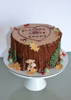 Tree Stump Groom's Cake with edible woodland decor, including acorns, ladybugs, oak leaves, fiddleheads, fern fronds, and butterflies. Image copyright Carla Reich.