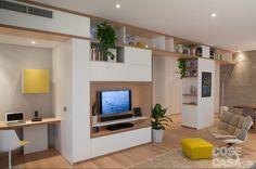 Legno protagonista a pavimento e parete nella casa di 125 mq con un originale blocco multifunzione a dividere il soggiorno dalla zona di servizio con ingresso, cucina e bagno.
