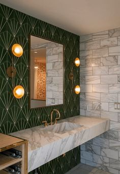 Eclectic bathroom with green patterned tiles on one wall and tiles with marble effect on the other. The sink furniture is additionally in marble and together with the brass elements, is creates an exclusive look.