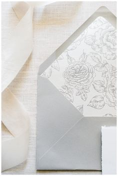 Outer wedding invitation envelope in soft, dove gray with botanical floral print lining from Written Word Calligraphy + Design. Image by Rustic White Photography.