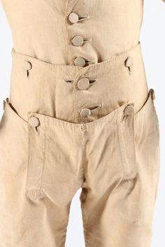 Detail front closure, boy's skeleton suit, c. 1785-1795. Buff nankeen cotton, self-covered buttons, the breeches buttoning onto the waist front and back, narrow sleeves, simple lapels, the trousers with small falls, and pockets to the sides.