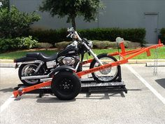 """Single Ramp Free Motorcycle Trailer $1895.00 Uses 2"""" Ball Length 140 inches Width 62 inches Weight Capacity 1200 LBS. Trailer Weight 400 LBS. 800 LBS. Brake Winch Dual Safety Pin Locks Single Rail/Rear 10 inches Wide Self-locking Chock Leaf Srings 950 LBS. Each Grease Fittings for Axle Grease Fittings for Spindles 12 Tie-Down Points Available 13"""" Tires.  Call for more information: 1-800-897-4430"""