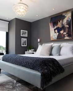 This sophisticated, modern bedroom features a charcoal gray and white color scheme with an elegant chandelier and colorful abstract art above the headboard as the focal point of the space.