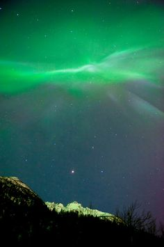 An aurora borealis corona bursts over the Chugach Mountains near the Knik River, north of Anchorage, Alaska.