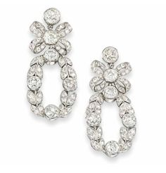 A PAIR OF EARLY 20TH CENTURY DIAMOND EARRINGS Of garland design, each single stone cirular-cut diamond surmount to a diamond-set bow link and further foliate wreath drop, circa 1900, 3.6cm long, post fittings, later adapted