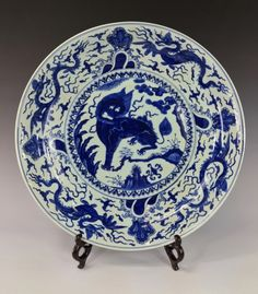 "A Fine Chinese Ming Blue and White Porcelain Dish, the center interior decorated with a kirin standing fiercely on a rock-work against trees. Interior rim decorated by winged sea dragons flying amidst flaming clouds. 19-1/4"" W"