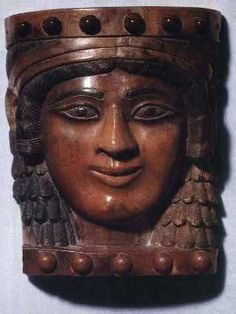 Assyrian ivory plaque head representing Ishtar, 725 B.C. She has been nicknamed the Mona Lisa of Nimrud, her hair has been painted black and the artwork is originally believed to have been attached to a piece of furniture. Her delicate oval face and smile is enchanting. Iraq museum, Baghdad