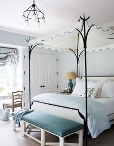 Black iron pointed canopy bed and black iron chandelier with hanging milk glass give the perfect amount of grounding in this lovely and light-filled blue and white bedroom. Love the print on the relaxed roman shade, the pops of teal from the lamp and the upholstered bench cushion, and especially the white turreted canopy with blue ribbon trim.