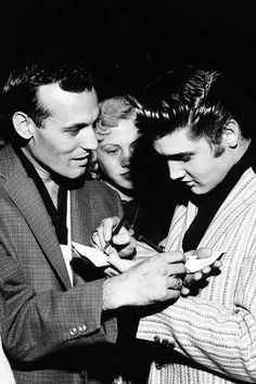 Carl Perkins and Elvis Presley swap autographs at the Overton Park Shell, Memphis, June 1, 1956. Photo by Alfred Wertheimer.
