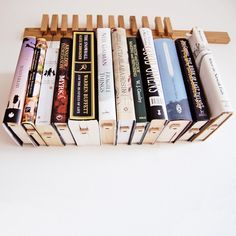 Fab.com | Book Rack Oak  books suspended by a loop of string with a small block at the bottom.  I wouldn't display any books of value this way, but it's quite charming.