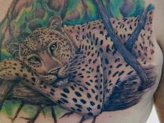 Leopard resting on a tree tattoo on chest