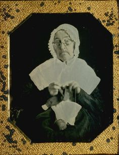 Elderly woman in mob cap and fichu crocheting ?stocking?, location unknown, 1850s?
