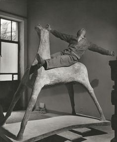 Italian sculptor, Marino MARINI, in his studio on one of his horses. Milan Italy 1952. Herbert List
