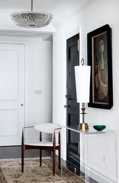 Entry vignette with delicate Italian mid century chair, glass light fixture, waterfall lucite console table, and stylized portrait