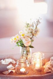 Table centrepiece idea - I like that this is not symmetrical and the candles are in jars that don't match.