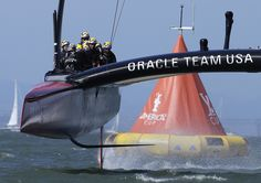 Oracle Team USA crosses the finish line during the 18th race of the America's Cup. (AP Photo/Ben Margot)