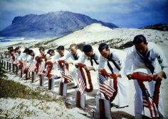 Uniformed American sailors place leis over the graves of their brothers in arms, in Spring 1942.