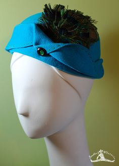 """The """"Celeste""""  Lovely aqua wool with vintage button and peacock feathers. Top-stitched with green embroidery thread to match vintage button. The combination of colors matches the peacock feathers so beautifully... this is truly a stunning hat in person! Has a 1930s feel. Vintage-inspired but with a modern flair. I enjoy playing with materials and this hat was a joy to make! I hope you love it as much as I do!  $80"""
