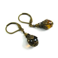 This is an exquisite pair of delicate Neo Victorian earrings. They feature mottled tortoiseshell colored Czech glass beads with layered filigree