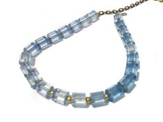 This cute vintage necklace features faceted light blue transparent plastic beads, small brass bead spacers, and a cable chain adjustable up to 17