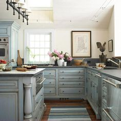 Never thought of blue cabinets -- add blue patina with French blue-painted cabinets gain the look of age with a distressed texture and a taupe glaze that clings to their door and drawer fronts, turned legs, and crown molding. Concrete countertops and stai Shabby Chic Kitchen Cabinets, Distressed Kitchen Cabinets, Glazed Kitchen Cabinets, Gray Cabinets, Upper Cabinets, Custom Cabinets, Bathroom Cabinets, Kitchen With Blue Cabinets, Antique Glazed Cabinets