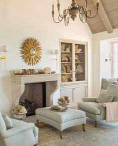 French and Swedish inspired sitting area in modern farmhouse romantic bedroom. Antique stone fireplace surround, buit-ins, aqua, wing chairs, wood ceiling, and French chandelier. Prepare to swoon over this Giannetti Home! {House Tour} French Country Beach House by Giannetti Home - Hello Lovely