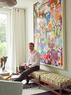 Nice painting.  The house owner is seated on a banquette in the living room - Hubert Zandberg Designer
