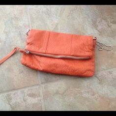 Orange Foldover Clutch Looks like Real leather material, but it's not. Does come with straps. Used a few times but excellent condition! Bought overseas Bags