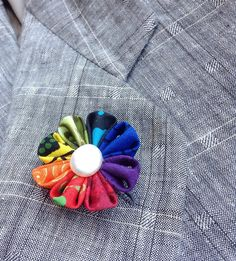 An elegant rainbow lapel flower pin boutonniere for men and women in the Japanese tsumami kanzashi style! This attention-grabbing design comes out a little differently every time, and each is an exclusive, so no one else can have this one! I used 8 different batik, African , Japanese and western cotton prints for the flower, glued a coin pearl into the flower center, and mounted everything on a tie tack with butterfly clutch back. Complements a suit, blazer, hat, vest, cardigan or sport…
