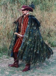 Created by Suzi Clarke Ramirez was based on 16th century men's clothes, and I have now made two reproductions in velvet based on his costume from the film Highlander. The peacock feather cloak, (the peacock is a symbol of immortality!), had no origin in anything I could find, but is strongly reminiscent of various native clothes such as the Maori and Inuit ceremonial cloaks.