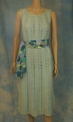DESCRIPTION: Hand-fashioned dress--simple, yet smashing! The open-weave design is SO in style--wear it with a coordinating or contrasting colored slip, or with no slip at all for a bare look. Versatile: Wear belted or not, or with a colorful scarf; with strappy sandals or boots. We estimate this is from the 60s to early 70s, in a soft seafoam color. Unsure as to yarn content--possibly wool/acrylic blend. Closely crocheted narrow panels are joined by an open shell stitch, and hem is made ...