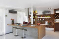 Parte da mostra promovida pela loja Leroy Merlin Rio de Janeiro, esta cozinha projetada pela arquiteta Letícia Araujo tem uma marcenaria criativa: os móveis foram feitos com portas de madeiras e a parede do fundo recebeu revestimento de pequenos tacos.