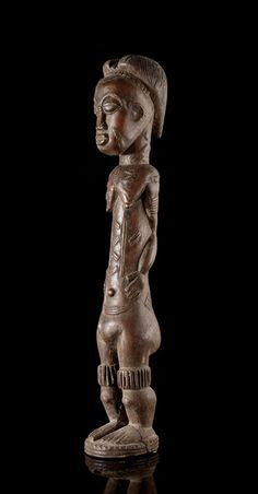 """A female Baule Figure, carved by a woman (!), called """"Nana"""", who lived and worked in Foué, a village not far from Bouaké, Ivory Coast. It is extremly rare, that a Baule-woman is working as a carver. , source: http://www.tribalartforum.com"""