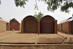 This cluster of dwellings provides housing for primary school teachers in the small village of Gando. Six houses fan out in a wide arc from a shared arrival point, marking the southern limits of the school site. Three housing types, each based on a module as large as a traditional round hut, are combined in various ways to form a more complex whole. — Kere Architecture | Teachers' Housing, Gando, Burkina Faso — Chicago Architecture Biennial