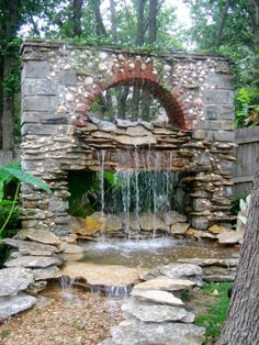 The open archway design adds a cool optical effect by making it look like the water is just appearing out of thin air. The blend of red brick, river stone, flag stone, and quarried rock gives this hardscape feature the look of a 19th century industrial structure that's been abandoned and overgrown.