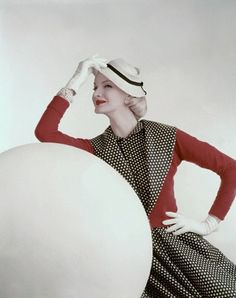 Model in a red, black and white polkadot ensemble, photographed by John Rawlings.