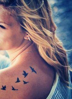 Little back tattoo of flying birds.