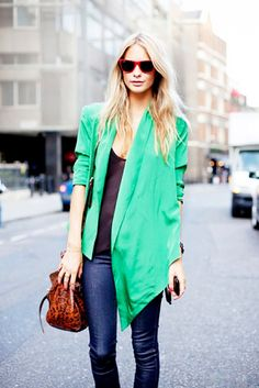 Poppy Delevingne wears a black tank top, silky green blazer, skinny jeans, red Ray-Ban sunglasses, and a leopard print bucket bag