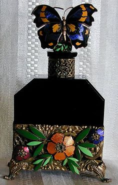 AUSTRIAN ART NOUVEAU PERFUME BOTTLE - A striking black glass and vividly colored enameled perfume bottle with enameled butterfly stopper and enameled & gilt metal floral mounts, signed Austria on foot