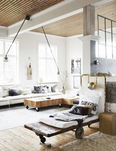 A Swedish living room with a large white sectional, and a reclaimed wood rolling coffee table