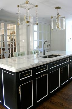 By Design Manifest - Black and White kitchen cabs - island with mirrored pantry, marble counter-top  and Lucite lighting - LOVE The Look!