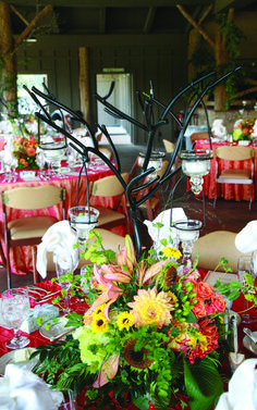 Centerpieces of orange and yellow blooms with tea light candles suspended from wrought-iron branches.