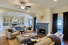 Grey and Cream Living Room created by Leslie Bannister Designs. Cream walls, white trim, dark wood floors, cream rug, taupe accents.