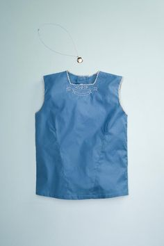 100% woven cotton sleeveless blouse. Sweet embroidery on front, back button closure and scalloped edges at neck and armholes.